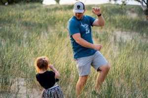Little girl dancing with father in a field